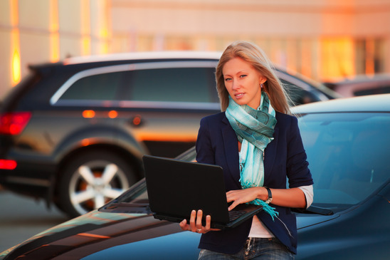 businesswoman-with-laptop-on-the-car-parking